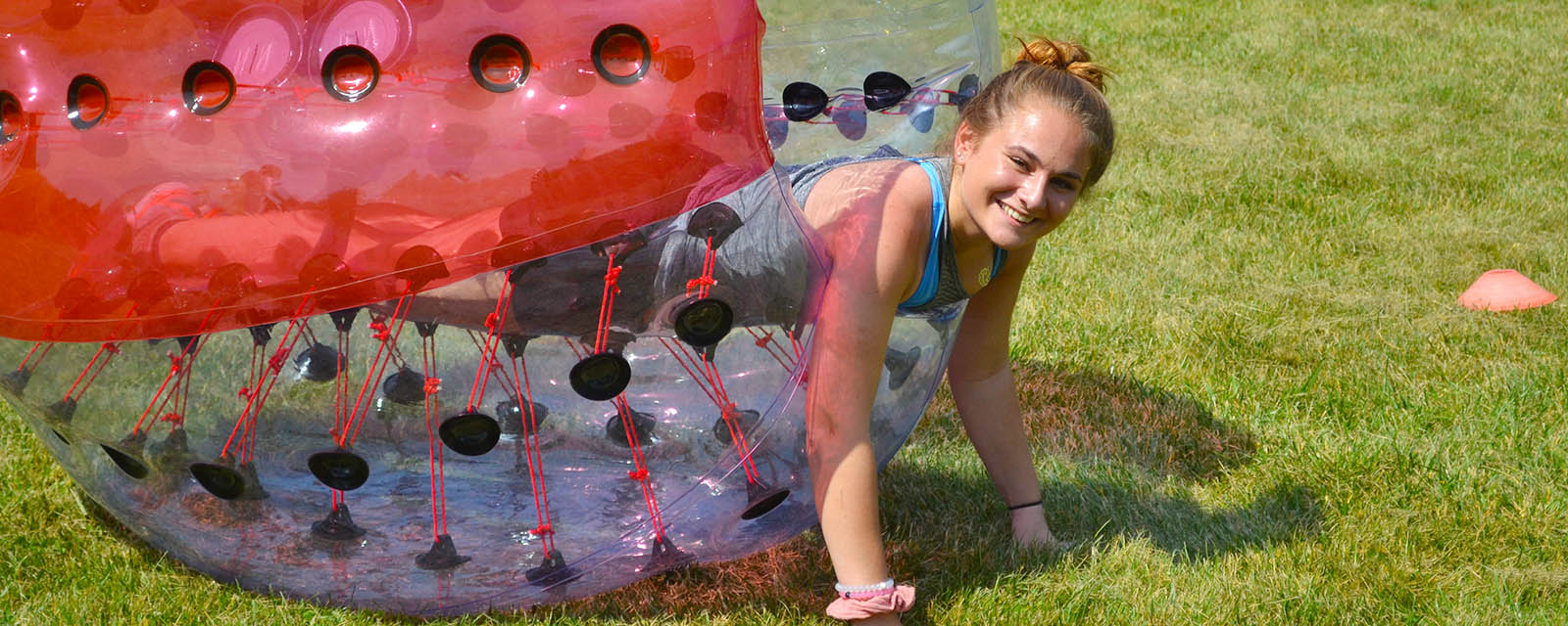 girl climbing out of giant soccer bubble