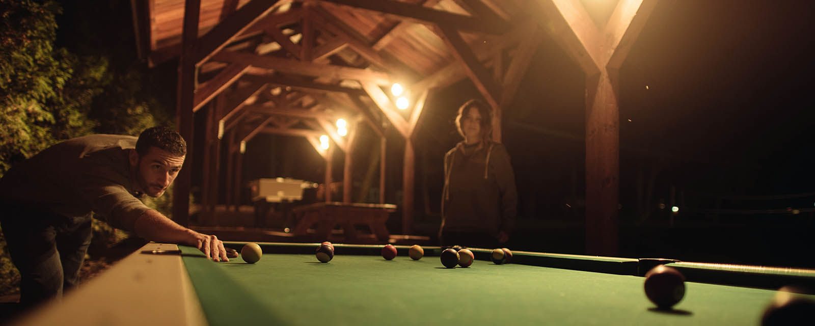 couple playing billiards at night